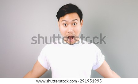 Surprised face and pose. An asian man with white t-shirt and grey background. - stock photo