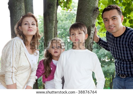 surprised family of four outdoors - stock photo