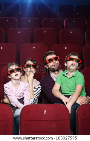 Surprised family watching a movie at the cinema - stock photo