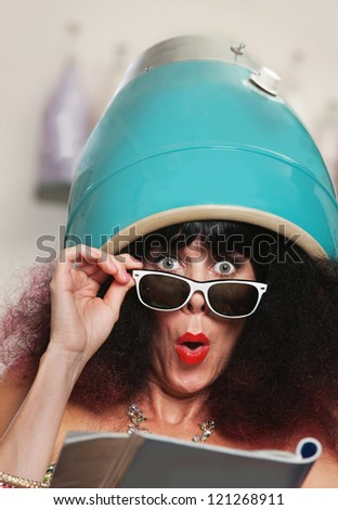 Surprised female reading magazine while under hair dryer - stock photo