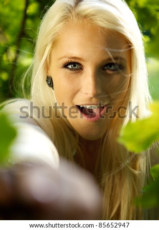 Surprised female standing amongst some trees in a forest. - stock photo