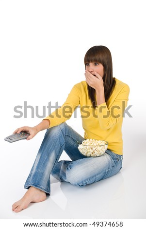 Surprised female teenager watching television holding remote control, eating popcorn - stock photo