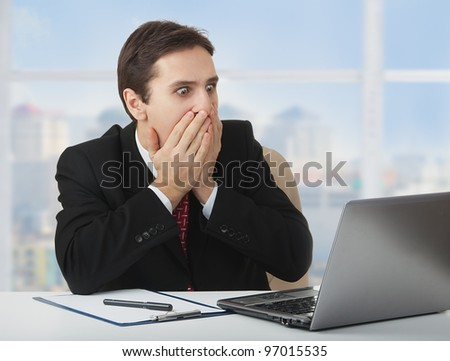 surprised  frightened businessman   looking at a laptop, his hands covering his mouth with fear and wonder, sitting at his desk - stock photo