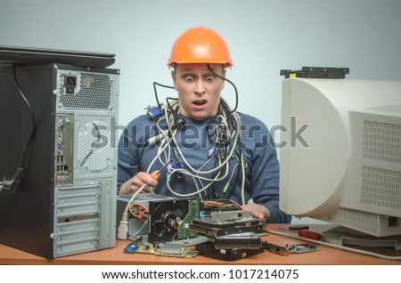 Surprised frightened computer repairman installed the computer components incorrectly. Computer technician wrapped in wires with screwdriver. PC repair service center.