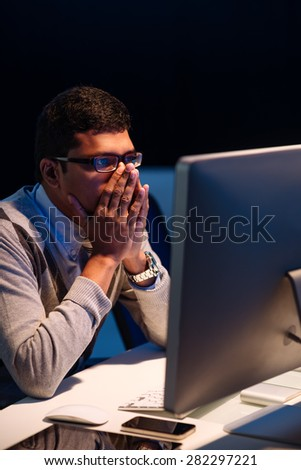 Surprised frightened office worker looking at computer screen - stock photo