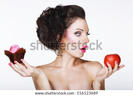 Surprised Funny Woman Decides between Apple and Cake - stock photo