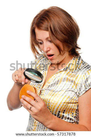 Surprised girl considers a hamburger through a magnifier - stock photo