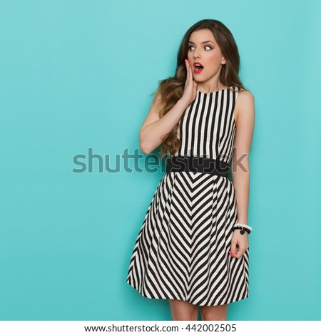 Surprised girl in black and white striped dress holding hand on chin and looking away, Three quarter length studio shot on turquoise background. - stock photo