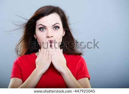 Surprised girl in red t-shirt with flying hair holding her hands near his mouth, over gray background - stock photo