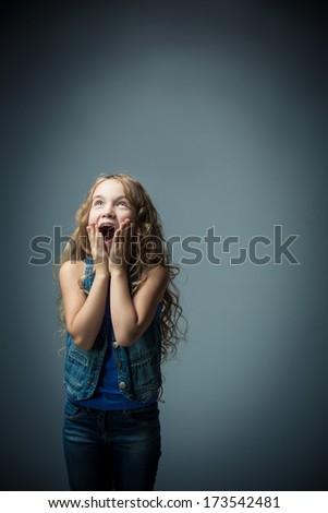 Surprised girl in studio - stock photo