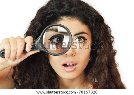Surprised girl looking through magnifying glass - stock photo