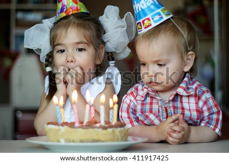Surprised girl near the candle on her birthday cake with her brother on the background, focus on the girl, happy birthday concept - stock photo