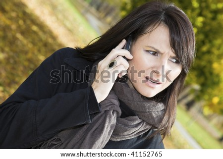 Surprised girl on the phone in the colorful park. - stock photo