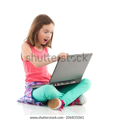 Surprised girl sitting on the floor with legs crossed and using the laptop. Full length studio shot isolated on white.