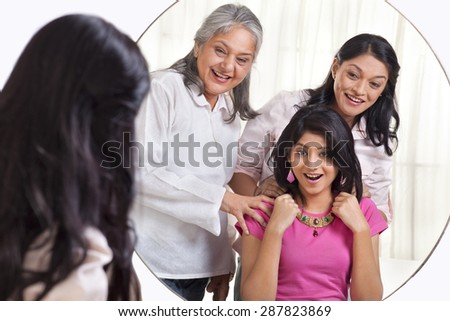 Surprised girl wearing necklace gifted by her grandmother and mother - stock photo