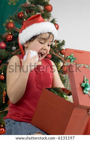 surprised girl wearing santa hat opening  a gift in front of a blurred decorated tree - stock photo