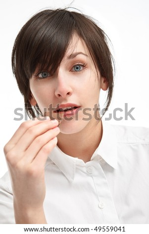 surprised girl with big blue eyes holding a piece of chocolate in hand - stock photo