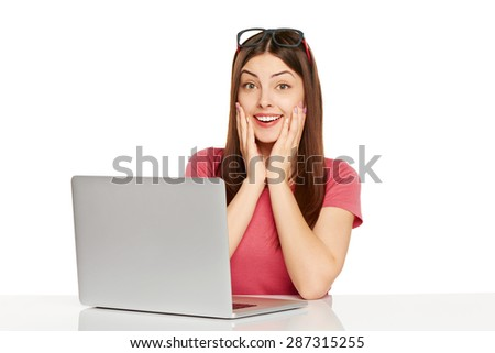 Surprised girl with laptop with hands on cheeks, sitting at table over white background - stock photo