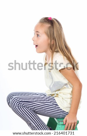Surprised girl 7 year old  is surprised as she sits on stool