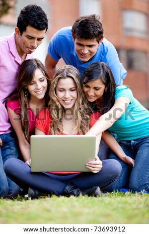 Surprised group of friends looking at a laptop outdoors - stock photo