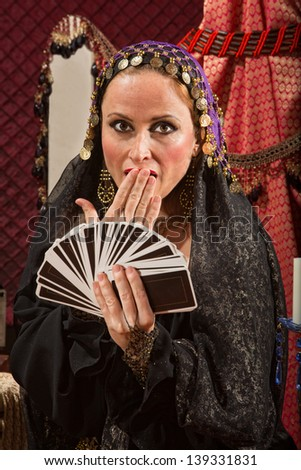 Surprised gypsy fortune teller with hand of tarot cards - stock photo
