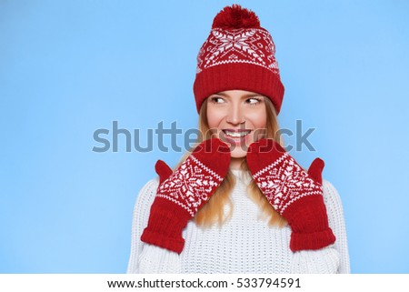 Surprised happy beautiful woman looking sideways in excitement. Christmas girl wearing knitted warm hat and mittens, isolated on blue background