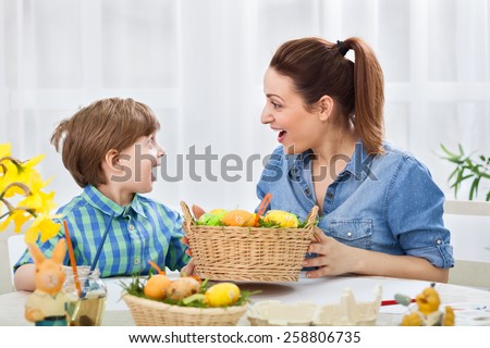 Surprised happy family holding easter eggs - stock photo