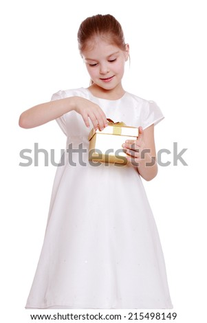 Surprised happy little girl in a beautiful dress opens gift isolated on white - stock photo