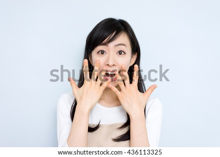Surprised housewife with apron sing against light blue background - stock photo