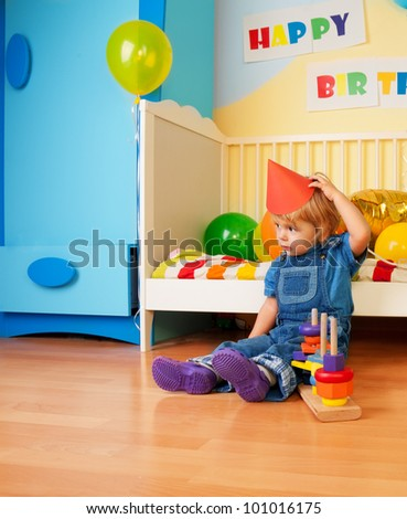 Surprised kid after birthday party sitting on the floor and holding cap
