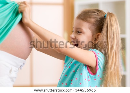 surprised kid girl looking at pregnant mother belly - stock photo
