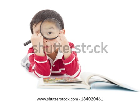 surprised kid looking through from magnifying glass - stock photo