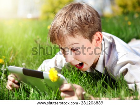 Surprised Kid with Tablet Computer on the Summer Meadow - stock photo