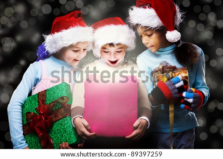 Surprised kids in Santa hats looking inside the present box - stock photo
