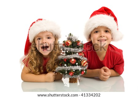 Surprised kids with small decorated tree at christmas time - isolated - stock photo