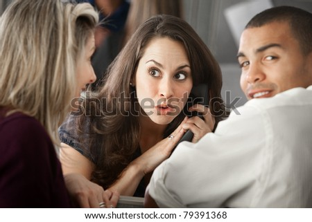 Surprised Latina office worker on a phone call as co-workers listen - stock photo