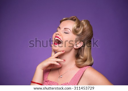 Surprised laughing beautiful young woman posing in photo studio. Studio shot of sexy blond girl with her eyes closed.