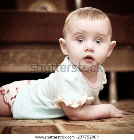 Surprised Little Baby on the Floor in Home Interior - stock photo