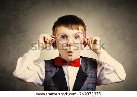 Surprised  little boy holding glasses isolated over grey  background. - stock photo