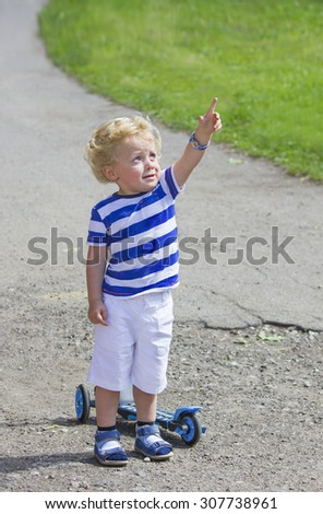 Surprised little boy showing to the sky on summer day - stock photo