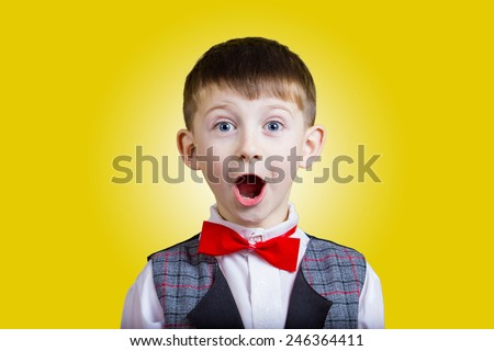 Surprised  little boy with mouth open isolated over yellow background. - stock photo