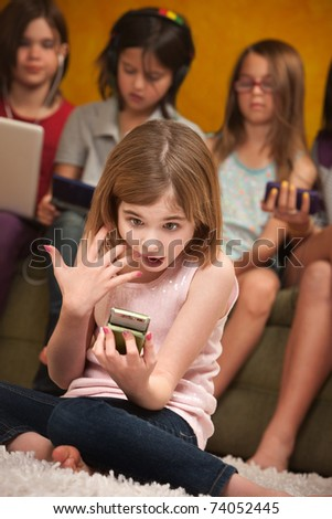 Surprised little Caucasian girl with a handheld device - stock photo