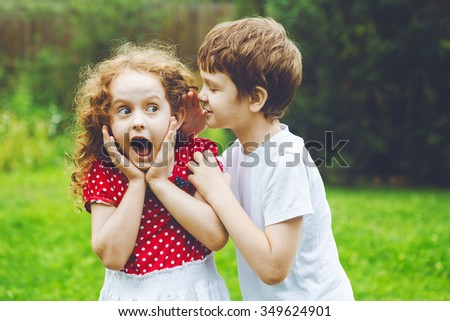 Surprised little girl and boy talking with whispers. Toning to instagram filter. - stock photo
