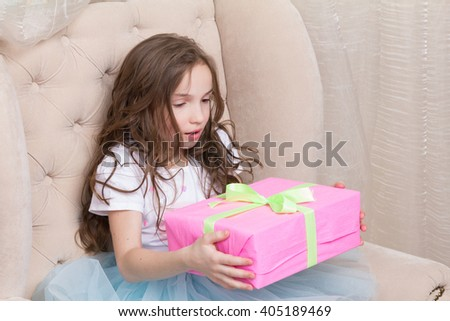 surprised little girl hold gift box - stock photo