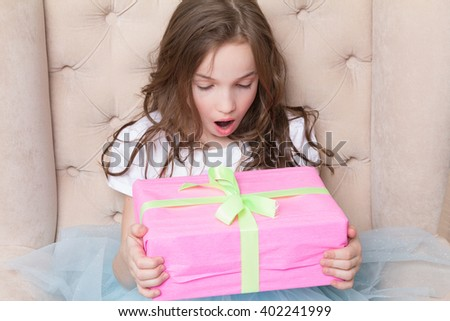 Surprised little girl hold pink giftbox tied with ribbon and bow. Girl sit on big chair - stock photo