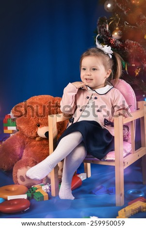 surprised little girl in purple jacket sitting on chair with toys on a blue background