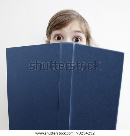 surprised little girl  looks in wide-eyed astonishment from book - stock photo