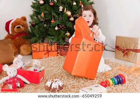 Surprised little girl opening Christmas-boxes - stock photo