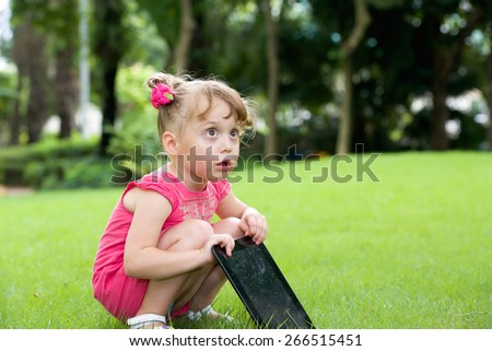 Surprised little girl outdoor with tablet pc on hands - stock photo