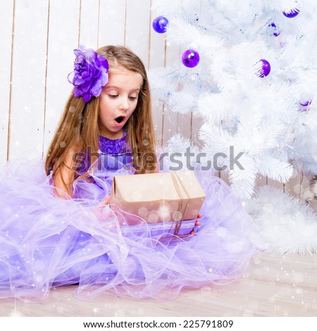 surprised little girl with a gift in hands near white Christmas tree - stock photo
